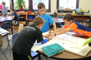 Students collaborate to chart the orbits of the planets.