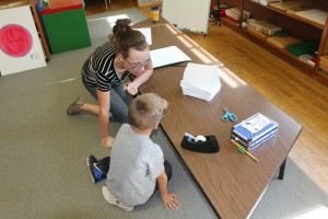 Becca Moore consults with a lower elementary student on construction of a paper model home.
