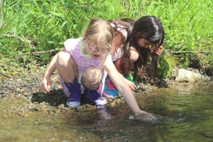 River Schroeder-Neal, left, and a classmate release trout into the wild.